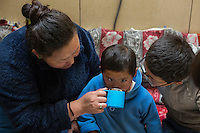 Tibetan carer Lhakdon helps a young visually impaired Tibetan student take a flu tablet at the kitchen of the School for the Blind in Tibet, in the capital city of Lhasa, September 2016.