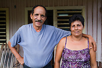 Cuban couple pausing in front of their wooden home in Vinales, Pinar del Rio Province, Cuba.