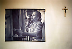 An old poster photograph of Eva Peron making a speech to her followers from the balcony of the Casa Rosada ( the presidential palace ) hangs next to a crucifix in an office in Buenos Aires. 2002 2000s