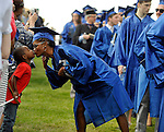 Marching in the line comes to a temporary halt time for a quick kiss between Chonette Johnson of Manchester and her 4-year-old son Javion, about to receive her degree in general studies, during the fiftieth Manchester Community College Commencement Exercise, Thursday, May 28, 2014, at the band shell at MCC. (Jim Michaud / Journal Inquirer)