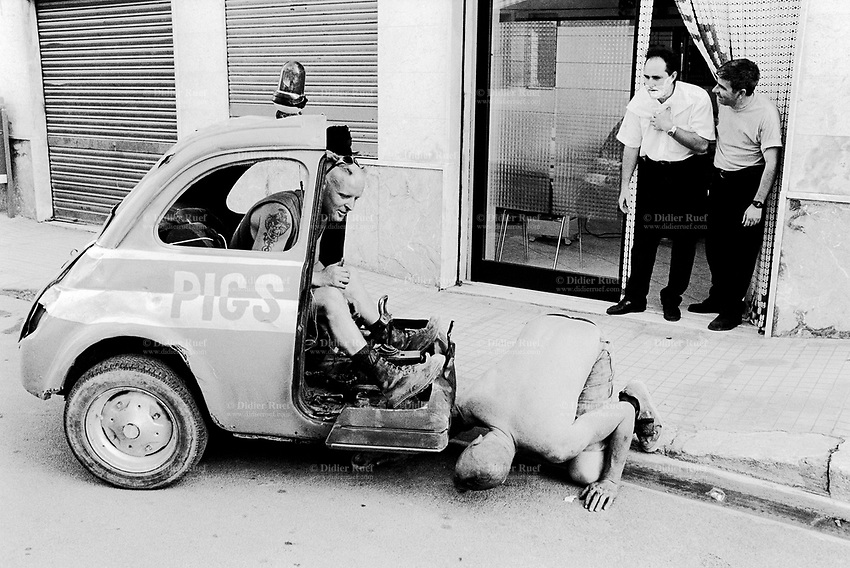 "Italy. Province of Sicily. Menfi. Mutoid Waste Company.  A man drives and tests the Fiat 250 (a Fiat 500 cuts in half) before the start of the show at ""Inycon"" festival. Two other men look at the scene in front of a barber shop. One man has shaving cream on his face. Using all types of industrial scrap for their raw materials the Mutoid Waste Company are a mobile and adaptable group of performance artists. Having the necessary equipment to allow them complete freedom, they have created an entirely new form of scultural-musical performance crossing the boundaries of circus, theatre and art. © 1999 Didier Ruef"