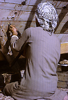 Kuwait April 1967.  Chiseling Holes to Receive the Head of Long Spikes to be Driven into interior Bracing of a Dhow's Hull.