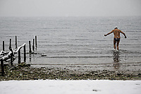 Pictured: A man braves the freezing cold weather and snow to go swimming on Aretsou beach near Salonica, northern Greece. <br /> Re: Heavy snow has affected most areas of Greece.