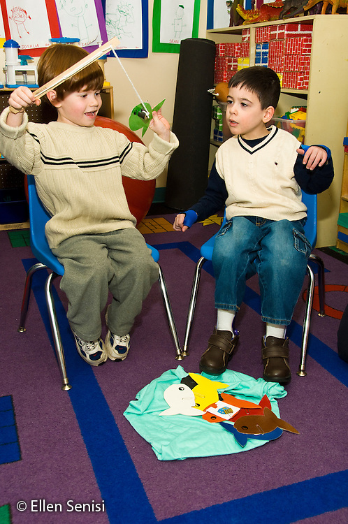 MR / Albany, New York. Clover Patch Early Childhood Day Care classroom. Clover Patch is an inclusion early childhood education program with disabled and non-disabled students at Center for Disability Services, an ungraded private school that serves individuals with disablilities. Students in inclusion classroom play fishing game with magnets to pick up and identify sight words. Left: boy, 4; right: boy, 5, Cuban-American / Caucasian, Cerebral Palsy, Spastic Diplegia, mainstreamed in inclusion classroom. MR: One1, Cal8. ID: AH-gPcp. ©Ellen B. Senisi.