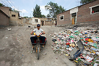 A resident drives through a Uyghur community called 'Yamalik Hill', a poor area in central Urumqi, in China's western Xinjiang Province.