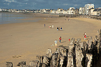 People walking along the beach at Saint-Malo, Brittany, France.