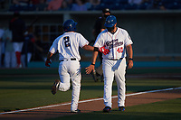 Victor Torres (2) of the Kannapolis Cannon Ballers slaps hands with third base coach Guillermo Quiroz (40) after hitting a home run against the Columbia Fireflies at Atrium Health Ballpark on May 21, 2021 in Kannapolis, North Carolina. (Brian Westerholt/Four Seam Images)