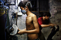 """A textile worker wearing a face mask distresses a pair of jeans using a sanding machine at a garment factory. The factory, which specifically carries out a wear-and-tear process used to achieve a fashionable distressed look, produces approximately 10,000 pairs of jeans every day. Thousands of workers labour through the night scrubbing, spraying and tearing jeans in order to meet the production demand. The factory is owned by Huang Dehong, who left his impoverished village and arrived penniless in Zhongshan twenty years ago. China, the """"factory of the world"""", is now one of the world's largest producers of jeans and its textile workers are among the 200 million migrant labourers criss-crossing the country looking for a better life."""