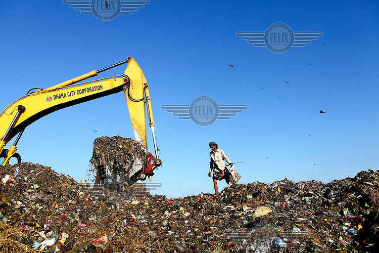 A man looks for recyclable material at the biggest rubbish dump in Dhaka. The city alone generates about 3500 to 4000 metric tons of solid waste each day.