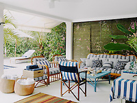 Wicker chairs and a sofa on the poolside terrace are upholstered in a Bergamin striped fabric