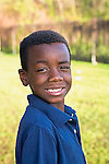 One black seven years old boy smiles broadly over his shoulder outdoors in portrait