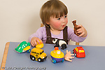 17 month old toddler girl playing with toy vehicles and toy animals mental categorization holding two toys of the same type caucasian