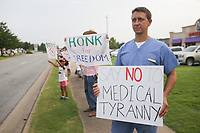 """William Smith, a chiropractic doctor at Central Chiropractic in Alma, holds up a sign, Sunday, August 1, 2021 during a March for Mercy rally along the sidewalk of South Promenade Blvd. in Rogers. """"This is an experimental vaccine. It has not finished clinical trials,"""" he said of why he distrusts the vaccine. """"It makes me angry when we hear all of these things being spewed in mainstream media and they're turning the vaccinated against unvaccinated. I have no problem with people getting the vaccine but when you force it on people that's another thing."""" Hundreds came out to protest the covid-19 vaccine mandate for Mercy Hospital employees. Mercy will require all workers to be vaccinated by September 30.  Check out nwaonline.com/210802Daily/ for today's photo gallery. <br /> (NWA Democrat-Gazette/Charlie Kaijo)"""