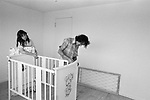 Putting up the babys cot, father eldest daughter they have just moved into a new family home. The removal men have left and they are getting everything ready for their first night in the new family home. New estate Milton Keynes Buckinghamshire 1970s UK 1977