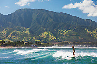 A woman surfs on the North Shore of O'ahu, with Mount Ka'ala in the background.