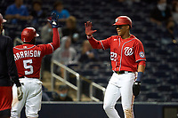 Washington Nationals Juan Soto (22) high fives Josh Harrison (5) after scoring a run during a Major League Spring Training game against the Miami Marlins on March 20, 2021 at FITTEAM Ballpark of the Palm Beaches in Palm Beach, Florida.  (Mike Janes/Four Seam Images)