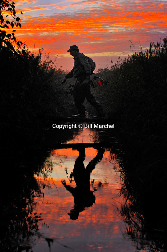 00105-039.12 Bowhunting (DIGITAL) Archer is silhouetted and carrying bow as he crosses log bridge on creek. Hunting, sunset, sunrise.  V4L1