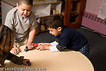 Education Preschool 4-5 year olds two boys and girl running small toy vehicles cars on table surface horizontal