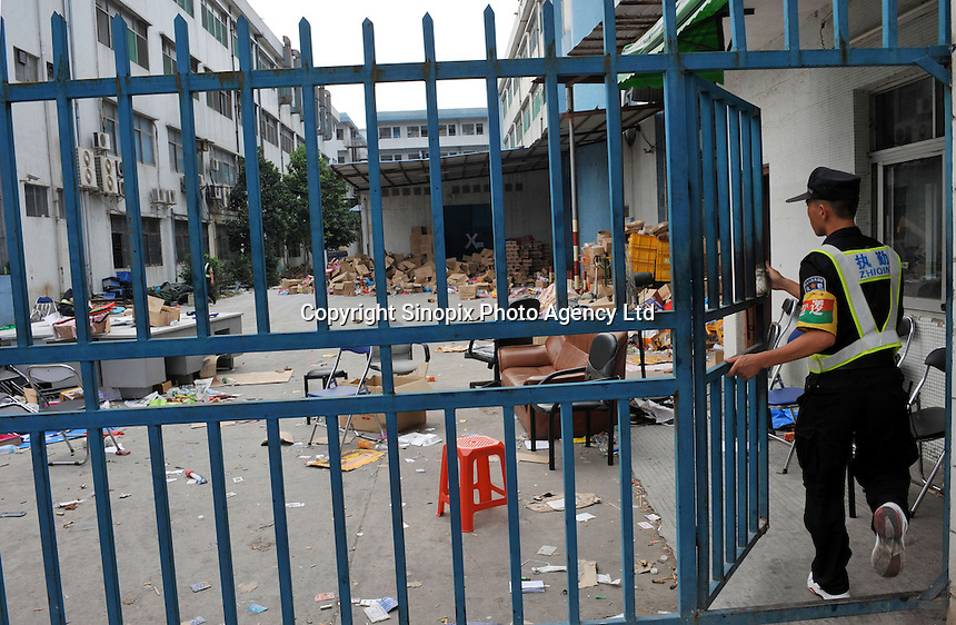 A security guard passes through the closed factory gates belonging to Smart Union, one of several factories in Zhang Mutou in South China that went bankrupt in the current credit crisis. Smart Union, that produced toys for ....Mattel amongst others, left 6,000 workers jobless and penniless after they could not pay the salaries. Hundreds of factories in South China are closing due to increased labor and material costs and the current credit crissis is exasperating. The problem leaving ghost towns behind. .24 Oct 2008