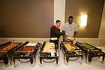 Aaron Craft puts some food on Evan Ravenel's plate during dinner