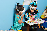 Education preschool 4 year olds two girls in dressup hats they made themselves talking and interacting, with open picture book