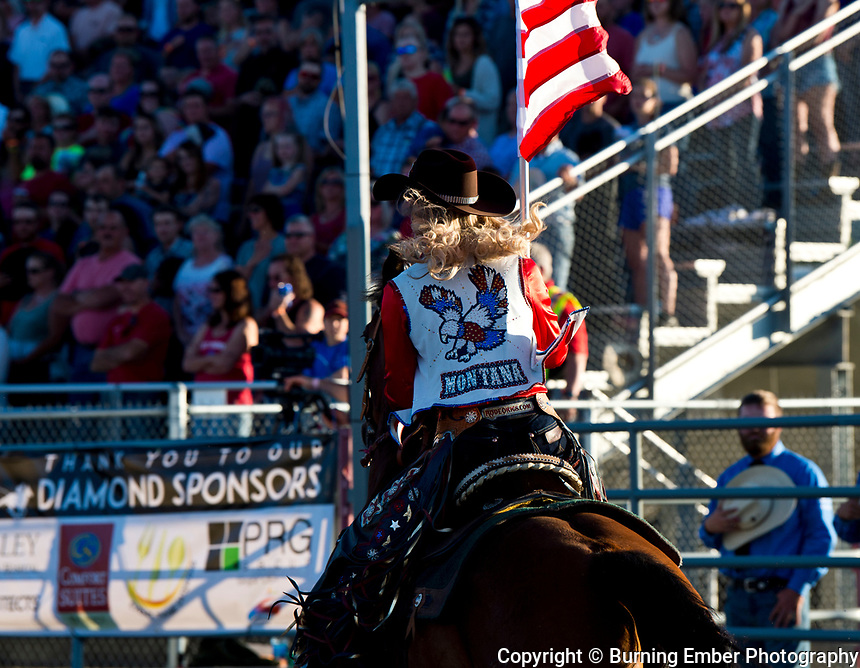 Kayla Seaman carrying the stars and stripes in the opening at the Helena MT Last Chance Stampede 1st perf July 25th 2019.  Photo by Josh Homer/Burning Ember Photography.  Photo credit must be given on all uses.