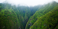 An aerial view of Sacred Falls with clouds hovering over the top of the Ko'olau Mountains, O'ahu.