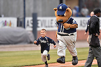 Asheville Tourists mascot Ted E Tourists races a young fan between innings of a game against the Lakewood BlueClaws at McCormick Field on May 4, 2016 in Asheville, North Carolina. The Tourists defeated the BlueClaws 2-0. (Tony Farlow/Four Seam Images)