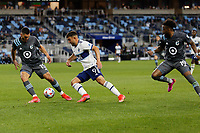 SAINT PAUL, MN - MAY 12: Lucas Cavallini #9 of Vancouver Whitecaps FC passes the ball past Michael Boxall #15 of Minnesota United FC during a game between Vancouver Whitecaps and Minnesota United FC at Allianz Field on May 12, 2021 in Saint Paul, Minnesota.
