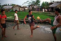 Men play football in Hlaing Thaya slum district of Yangon.