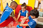 Education Preschool 3-4 year olds small group at water table one boy shorter than the others
