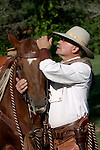 A cowboy whispering in the ear of his horse