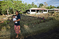 A young woman from the neighbouring village of Vaovai, which was also wiped out by the tsunami, clutches her baby and surveys the damage to Poutasi village. More than 170 people died when a tsunami triggered by an 8.3 magnitude earthquake hit Samoa and neighbouring Pacific islands on 29/09/2009. Samoa (formerly known as Western Samoa)..