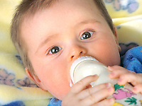 Close up of a toddler boy's face with a baby bottle and blanket