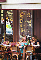 Le Bistrot du Peintre cafe bar terrase outside seating on the sidewalk. Two young women having a drink and chatting on a wicker sofa and using a mobile telephone cell for texting sms The Bistrot du Peintre is an old fashioned Paris café cafe bar restaurant of art nouveau design with polished brass, mirrors and old signs