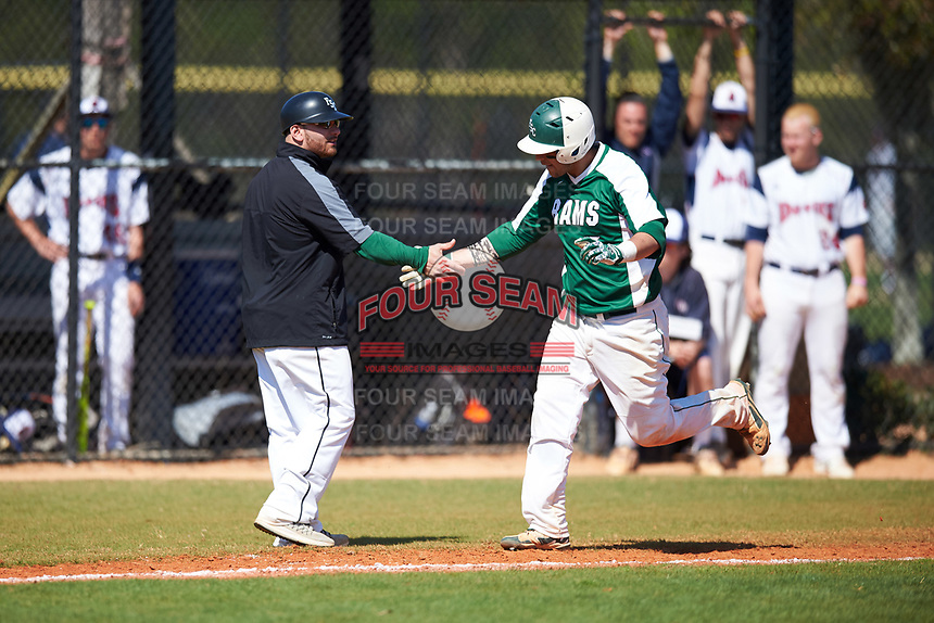 Farmingdale State Rams third base coach Anthony Alvino (left) congratulates Nick Osburn (5) after hitting a home run during the first game of a doubleheader against the FDU-Florham Devils on March 15, 2017 at Lake Myrtle Park in Auburndale, Florida.  Farmingdale defeated FDU-Florham 6-3.  (Mike Janes/Four Seam Images)
