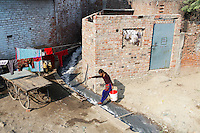 A young woman jumps over a waste water channel from a nearby leather-producing tannery. The water is laced with toxins from the leather treatment process and is discarded directly into water channels that run through the city.