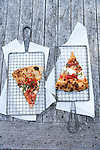 Two slices of Margherita pizza with fresh mozzarella cheese, tomato sauce, and fresh basil. On parchment paper under wire racks, on a weathered wood table.