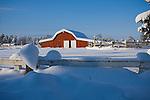 Idaho, Dalton Gardens, Coeur d' Alene. A red barn in a snowy landscape on a small farm.