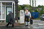 Greenfield, Saddleworth Yorkshire UK. Saddleworth Morris man with shopping trolley and wife.