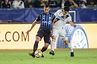 CARSON, CA - SEPTEMBER 21: Joe Corona #14 of the Los Angeles Galaxy and Saphir Taider #8 of the Montreal Impact battle for a ball during a game between Montreal Impact and Los Angeles Galaxy at Dignity Health Sports Park on September 21, 2019 in Carson, California.
