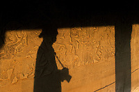 Shadow of a Tourist at sunset against the stone wall reliefs at Angkor Wat