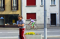 Switzerland. Canton of Ticino. Agno. Agno is 15 km distant from Lugano. A young girl stands alone near a traffic road. A man rides his bicycle as a leisure hobby on a sunny sunday afternoon. 22.05.05 © 2005 Didier Ruef