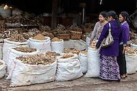 Myanmar, Burma.  Mandalay.  Women Examining Choices in the Dried Fish Market.