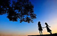 Two young girls are silhouetted as they dance at sunset  in Charlotte, NC.