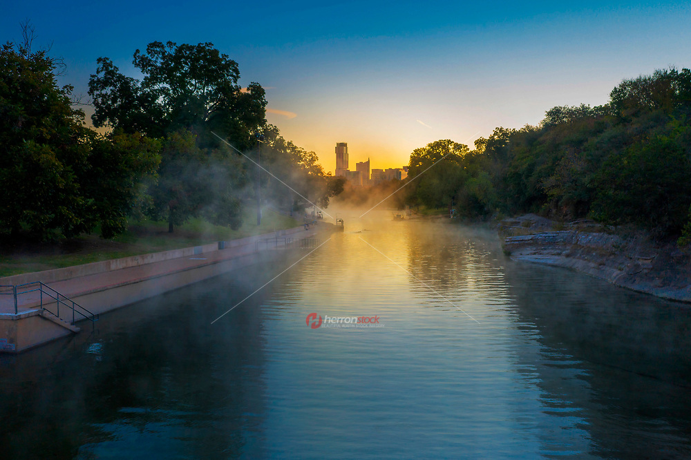 Swimmers take to Barton Springs Pool during a frigid winter's morning as steam rolls off the water of this natural spring pool situated in Austin's Zilker Park; inset the Austin skyline in the background.