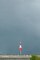 Dunkle Wolken und die Schweizer Landesflagge ueber der Schweizer Botschaft.<br /> Dark clouds above the Swiss embassy in Berlin.<br /> 23.4.2014, Berlin<br /> Copyright: Christian-Ditsch.de<br /> [Inhaltsveraendernde Manipulation des Fotos nur nach ausdruecklicher Genehmigung des Fotografen. Vereinbarungen ueber Abtretung von Persoenlichkeitsrechten/Model Release der abgebildeten Person/Personen liegen nicht vor. NO MODEL RELEASE! Don't publish without copyright Christian-Ditsch.de, Veroeffentlichung nur mit Fotografennennung, sowie gegen Honorar, MwSt. und Beleg. Konto: I N G - D i B a, IBAN DE58500105175400192269, BIC INGDDEFFXXX, Kontakt: post@christian-ditsch.de]