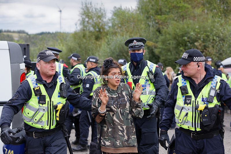 Pictured: A young woman is moved away by the police. Monday 31 August 2020<br /> Re: Around 70 South Wales Police officers executed a dispersal order at the site of an illegal rave party, where they confiscated sound gear used by the organisers in woods near the village of Banwen, in south Wales, UK.