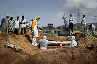 Relatives attend the funeral, at the King Tom cemetery, of a person who is suspected to have died from ebola. Due to the rapid increase in burials, caused by the ebola crisis, the cemetery is being enlarged and parts of a nearby rubbish dump is also being used to bury the dead.