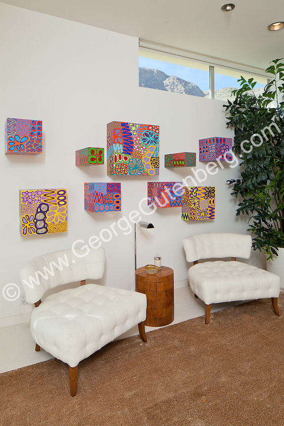 Colorful boxes seen on wall above white chairs